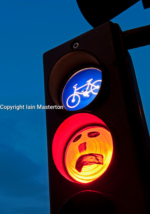 Sad face drawn onto red cyclist stop light at dusk in Berlin Germany