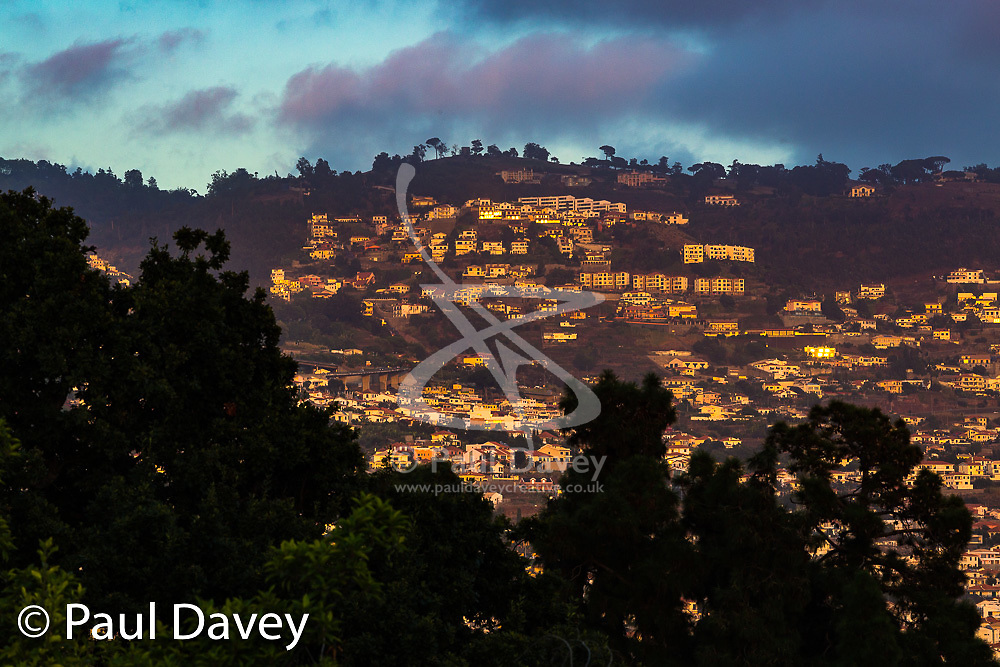 Houses on the steep slopes surrounding Funchal, capital of Madeira, are illuminated by the last rays of the setting sun. MADEIRA, September 25 2018. © Paul Davey