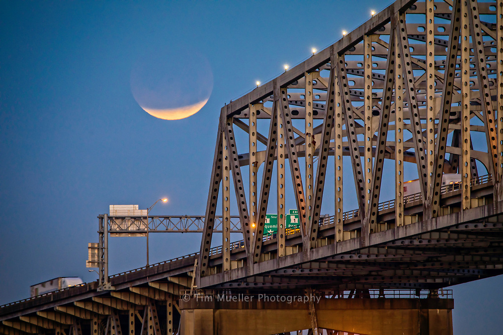 A lunar eclipse sets early Wednesday morning, January 31, 2018 over the Mississippi River and the Port of Greater Baton Rouge.