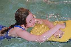 Young girl with learning disabilities swimming in public swimming pool using float,