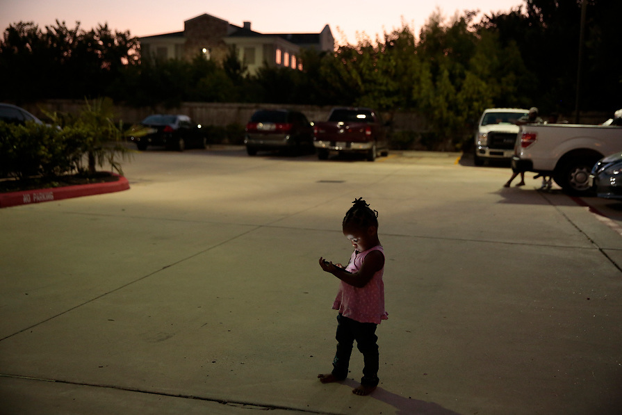 Elizabeth Thomas, 2, watches videos on her mother's phone outside their FEMA provided hotel room in the aftermath of tropical storm Harvey in Houston, Texas, U.S. September 10, 2017. Thomas' family lost all of their belongings in the flood and are living in a hotel room temporarily.
