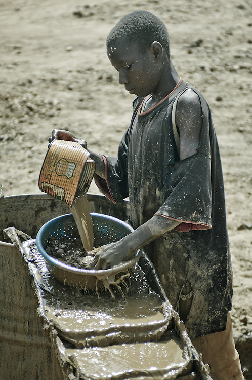 Stock photograph of an African gold miner in Burkina Faso processing the crushed ore to extract gold by sluicing
