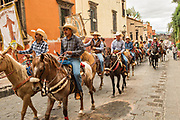A procession of Mexican cowboys ride through the streets on the final leg of their pilgrimage celebrating the festival of Saint Michael in San Miguel de Allende, Mexico.