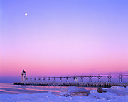 Moon setting at dawn over the South Haven South Pier Lighthouse in winter, entrance of the Black River into Lake Michigan, South Haven, Michigan.
