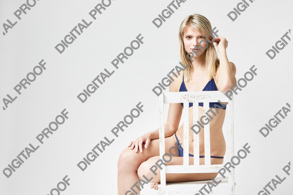 Portrait of seated woman in blue underwear at studio with a white background
