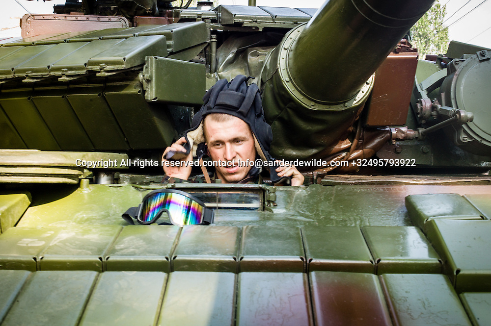 20150831 Moldova, Transnistria,Pridnestrovian Moldavian Republic (PMR) Tiraspol. Rehersal for the big parade, in the 25th  Transnistrian independance day when  they had a war separating from Moldova. A driver of a tank gets ready to leave, putting his hat on.