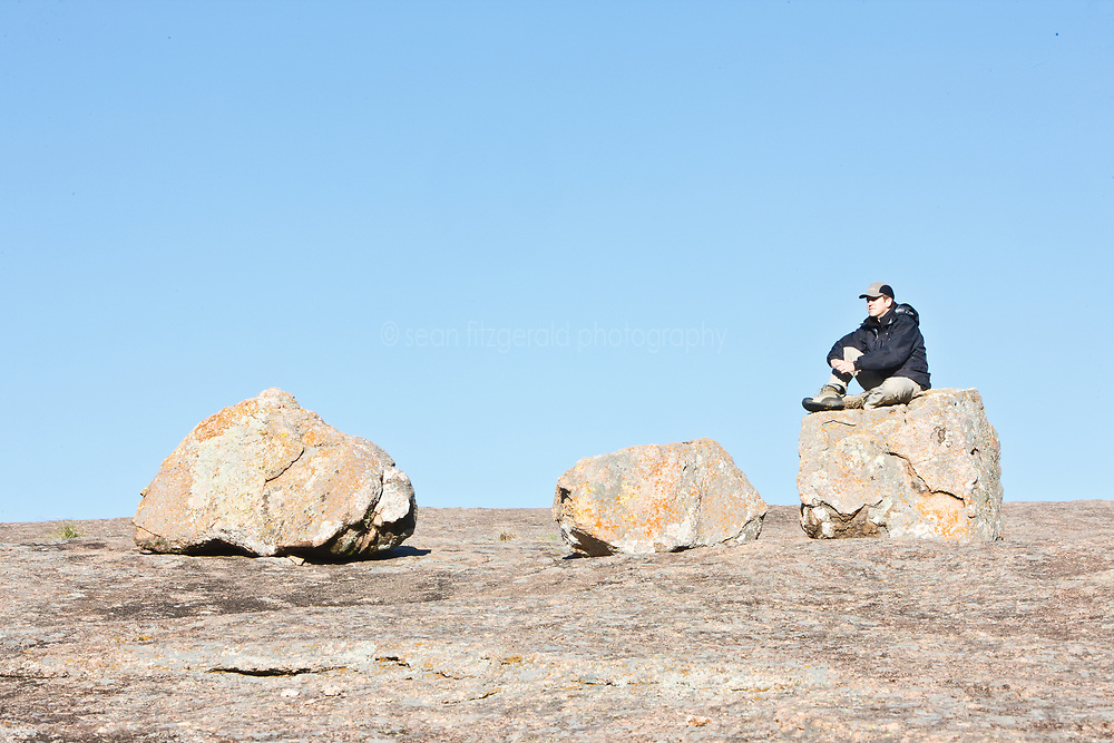 Hiker on Enchanted Rock boulder, Enchanted Rock State Natural Area, near Fredericksburg, Texas in the Texas Hill Country, USA.