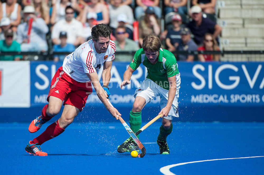 Simon Mantell of England is challenged by Ireland's Kirk Shimmins. Final of the Investec London Cup, Lee Valley Hockey & Tennis Centre, London, UK on 13 July 2014. Photo: Simon Parker