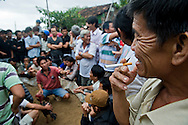 A vietnamese man smokes a cigarette while a rooster fight is interrupt.  Khanh Hoa area, Vietnam, Asia