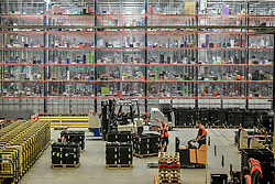 Workers move forklifts in front of huge racks containing thousands of items at Amazon's fulfillment centre in Swansea, in the run up to Black Friday.