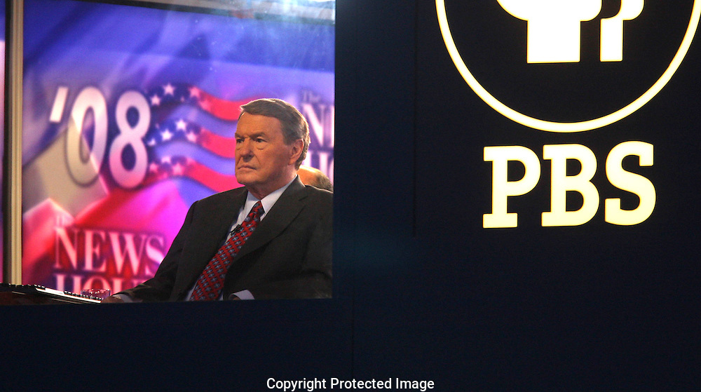 Jim Lehrer of PBS watches the proceedings at the second night of the Democratic Convention in Denver, Colorado. Photograph by Dennis Brack