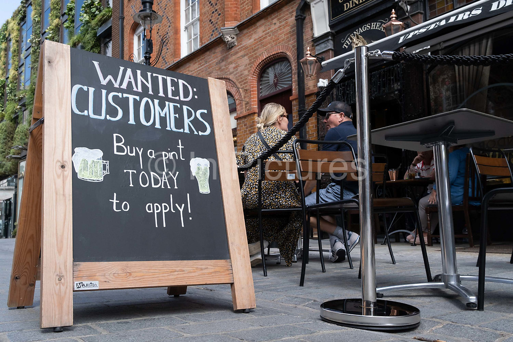 A sign outside a bar wants customers to return and help support their business in Covent Garden, on 20th August 2020, in London, England. (Richard Baker / In Pictures via Getty Images)