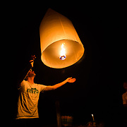 Andrew Whiteford, Jay Goodrich, Mr. Sak, and Win Jalawin release lanterns in a local tribe member's house in the higher altitude jungle near Ban Sop Gai, Thailand.