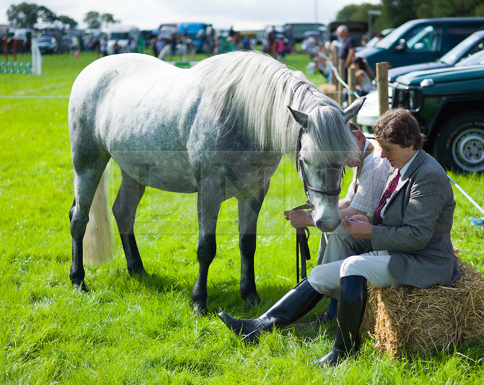 © Licensed to London News Pictures.12/08/15<br /> Danby, UK. <br /> <br /> A woman sits with her horse after competing at the 155th Danby Agricultural Show in the Esk Valley in North Yorkshire. <br /> <br /> The popular agricultural show attracts competitors and visitors from all over the surrounding area to this annual showcase of country life. <br /> <br /> Photo credit : Ian Forsyth/LNP