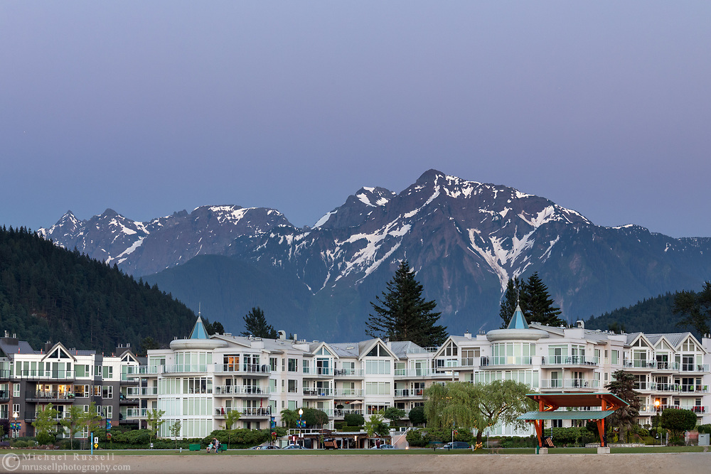 Waterfront condominiums with Mount Cheam in the background.  Photographed after sunset from the edge of Harrison Lake in Harrison Hot Springs, British Columbia, Canada.  The mountain peaks (from R to L) are Cheam, Lady, Knight, Stewart, and Welch.