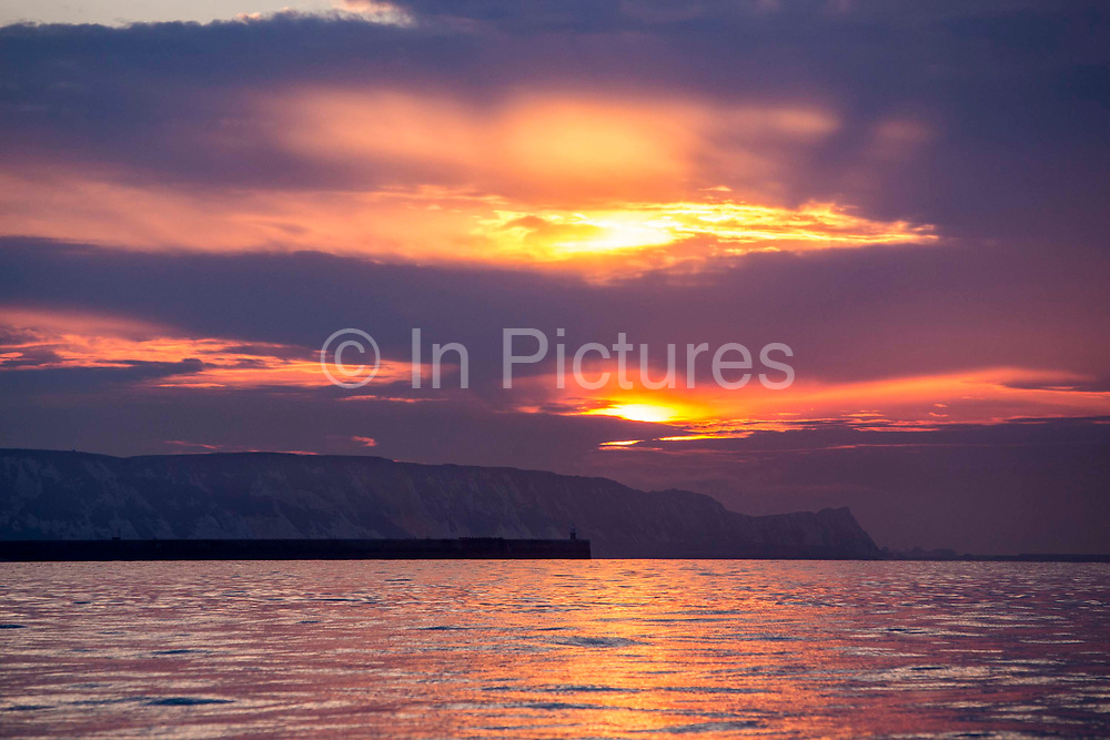Sunrise through large clouds over the White Cliffs of Dover, Folkestone Harbour Arm and The English Channel sea photographed from a boat off the coast of Folkestone, Kent, England, United Kingdom.