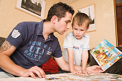 Polish father and son doing a jigsaw together,
