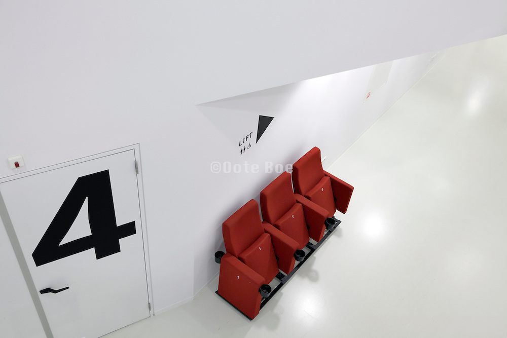 red cinema chairs near the entrance of the door to the film room