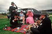 Royal Ascot racegoers picnic on the grass of an event car park, on 18th June 1992, in Ascot, England. Trays of food and two bottles of Champagne have been consumed during a break from betting and socialising. They are dressed in formal morning dress of top hat, waistcoat, tails with two of the men wearing red roses in their lapel button holes, all traditional and obligatory dress code in the Royal Enclosures which can be seen by visitors in the public car parks near the famous Berkshire race course. Royal Ascot is held every June and is one of the main dates on the sporting calendar and social season.