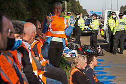 Ockham, UK. 21st September, 2021. Insulate Britain climate activists wait, under arrest by Surrey Police, on the hard shoulder of the M25 after blocking the clockwise carriageway between Junctions 9 and 10. Activists briefly halted traffic on both carriageways of the motorway as part of a campaign intended to push the UK government to make significant legislative change to start lowering emissions.