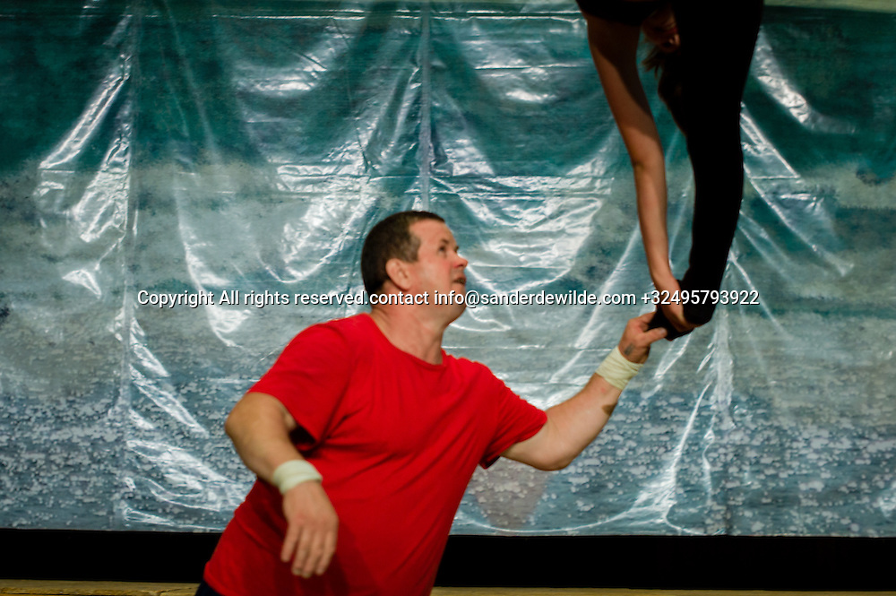 20150826 Bendery, Bender, Transnistria, Moldova.A trainer in a red shirt trains a girl hanging in a trapeze in a theatre in Bender, while exercising for a circus performance.