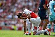 Olivier Giroud of Arsenal  holds his head injured after clashing heads with James Tomkins of West Ham United as they both jumped for the ball. Barclays Premier League, Arsenal v West Ham Utd at the Emirates Stadium in London on Sunday 9th August 2015.<br /> pic by John Patrick Fletcher, Andrew Orchard sports photography.