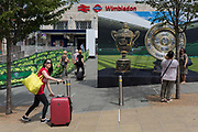 Passengers and pedestrians near a large hoarding showing the Mens and Ladies trophies, outside the Wimbledon railway station during the tennis championships, on 3rd July 2017, in Wimbledon, London, England.