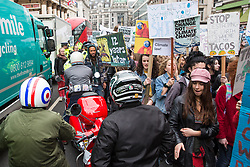 London, UK. 12th April 2019. Scooter riders heading to the Rolling Thunder Ride for Soldier F find themselves boxed in by students taking part in the third Youth Strike 4 Climate. After gathering in Parliament Square, students marched through central London. The strike was organised by UK Student Climate Network and the UK Youth Climate Coalition to demand that the Government declare a climate emergency and take positive steps to address the climate crisis.