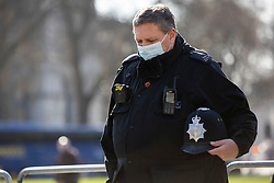 © Licensed to London News Pictures. 22/03/2021. London, UK. A police officer holds his helmet as he takes part in a minute's silence to remember those who lost their lives in the 2017 Westminster Bridge terror attack. Today marks four years since the attack and a commemorative plaque is expected to be installed on Westminster Bridge when Coronavirus restrictions are lifted . Photo credit: George Cracknell Wright/LNP