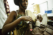 Marielle Gnabrayou Digbeto, 28, puts a pill bottle into her purse as she prepares to leave the pharmacy at the Koumassi general hospital in Abidjan Cote d'Ivoire on Friday July 19, 2013. Marielle is pregnant with her first child and HIV positive. She's taking drugs for eMTCT, but doesn't want people to know for fear of being rejected. She lives across town but comes to the Koumassi hospital so that nobody will find out.