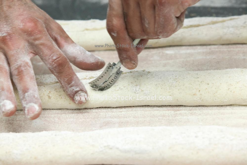 baker slashing dough to release internal tention while rising