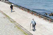 elderly man alone with walking stick and young couple Japan Yokosuka