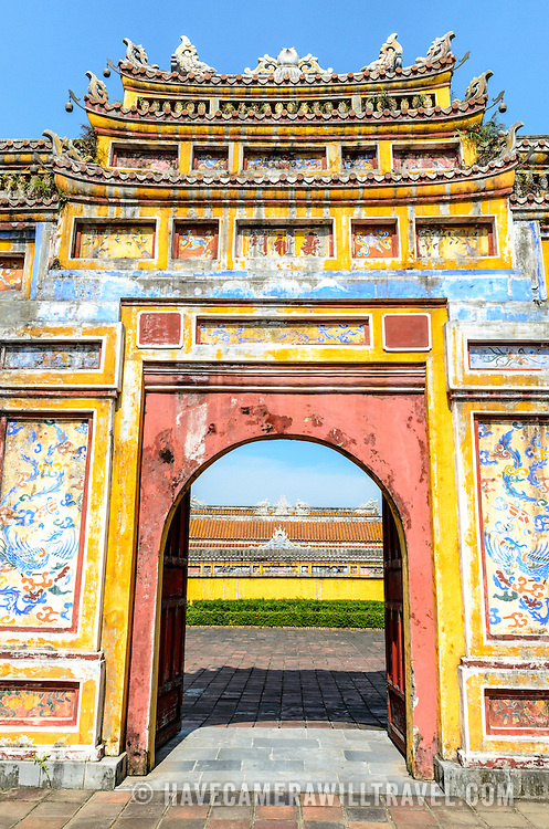 A painted gate at the Imperial City in Hue, Vietnam. A self-enclosed and fortified palace, the complex includes the Purple Forbidden City, which was the inner sanctum of the imperial household, as well as temples, courtyards, gardens, and other buildings. Much of the Imperial City was damaged or destroyed during the Vietnam War. It is now designated as a UNESCO World Heritage site. This gate was an entrance to the Dien Tho Residence. Constructed in 1804, this compound was was the Queen Mother's or Emperor's Grandmother's living quarters.