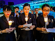 12 AUGUST 2018 - BANGKOK, THAILAND: Mall employees sing the royal anthem during a candlighting ceremony to honor the 86th birthday of Sirikit, the Queen Mother of Thailand at EmQuartier Mall in Bangkok. She was the wife of Bhumibol Adulyadej, the late King, and she is the mother of His Majesty King Maha Vajiralongkorn Bodindradebayavarangkun of Thailand, who succeeded his father. August 12 is also celebrated as Mother's Day in Thailand.    PHOTO BY JACK KURTZ