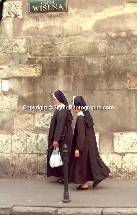 Nuns age 50 walking down the street in habits.  Krakow Poland