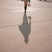 Pilot's shadow of the 'Red Arrows', Britain's Royal Air Force aerobatic team walking out to aircraft for training flight.