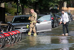 © Licensed to London News Pictures. 24/06/2021. London, UK. A man takes off his shoes and wades through a river of water to get to his car in St John's Wood, North London, where a burst pipe has has cause flooding across a number of streets in the area. Photo credit: Ben Cawthra/LNP