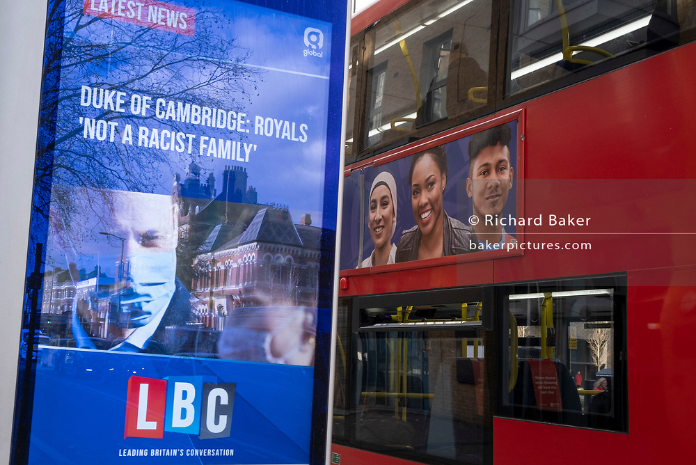 In response to Harry the Duke of Sussex and wife Meghan's Oprah interview last weekend, Prince William, a masked Duke of Cambridge responds with a denial, that the royal family is not a racist family, as reported on a digital news screen on the Walworth Road. A bus passes carrying an ad showing a multi-cultural population, on 11th March 2021, in London, England.
