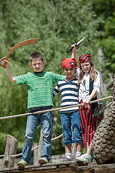 Three friends dressed up as pirates playing on pirate ship in adventure playground, Bavaria, Germany