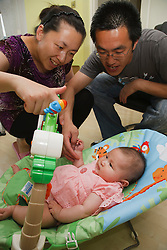 Chinese parents playing with baby in baby bouncer
