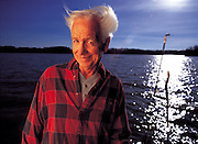 An old man smiles while standing on a pier fishing at a lake