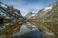 The snowy peaks of the Beartooth Mountains are reflected in the small Elk Lake. The water was calm before the wind picked up later in the morning.