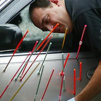 (PPAGE1) Asbury Park 9/13/2003  Det Sgt Steven Padula uses dowells to show the locations of the 18 bullet holes on a vehicle involved in a shooting in Asbury Park.     Michael J. Treola Staff Photographer.....MJT