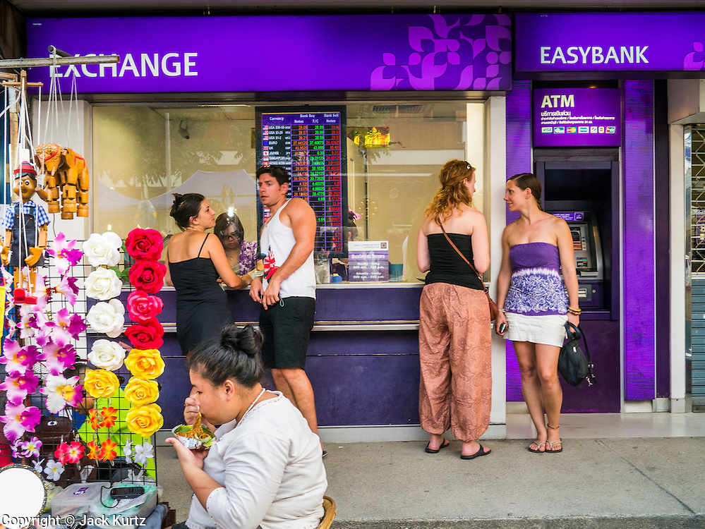 07 APRIL 2013 - CHIANG MAI, CHIANG MAI, THAILAND:  Tourists buy Thai Baht at a currency exchange in Chiang Mai, Thailand. The Thai Baht has surged against the Euro, Dollar and Pound Streling in the last year making Thailand comparatively more expensive for tourists and expats. Chiang Mai is the largest town in northern Thailand and is popular with tourists and backpackers.       PHOTO BY JACK KURTZ