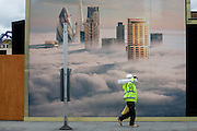 Construction workman walks beneath a property developer's billboard showing a large aerial image of London skyscrapers in low cloud.