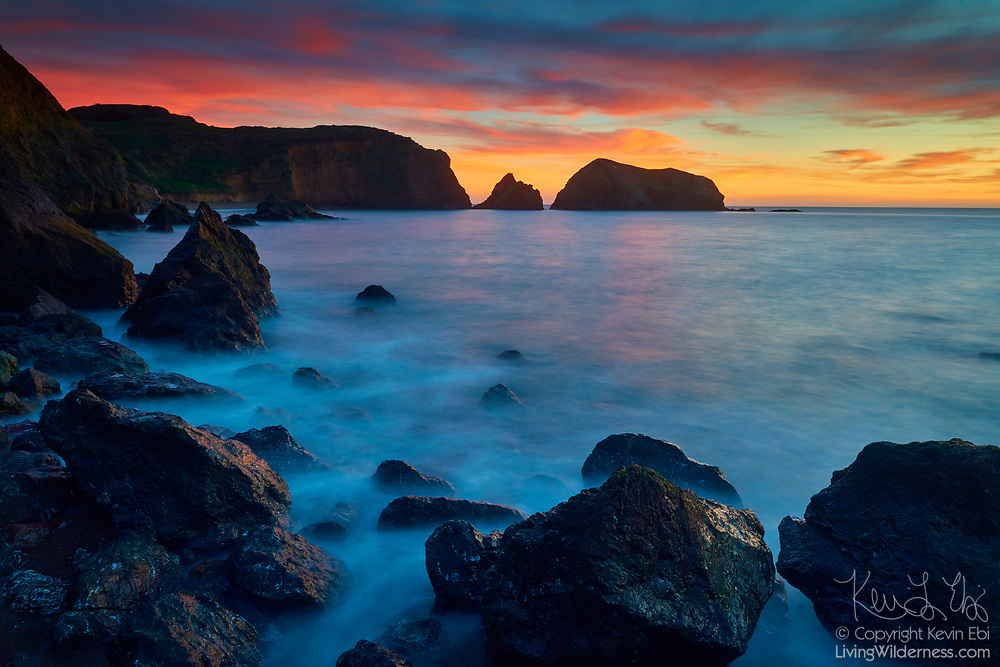 A fiery sunset colors the sky over Bird Island and the southern cliffs of the Marin Headlands, part of the Golden Gate National Recreation Area near San Francisco, California.