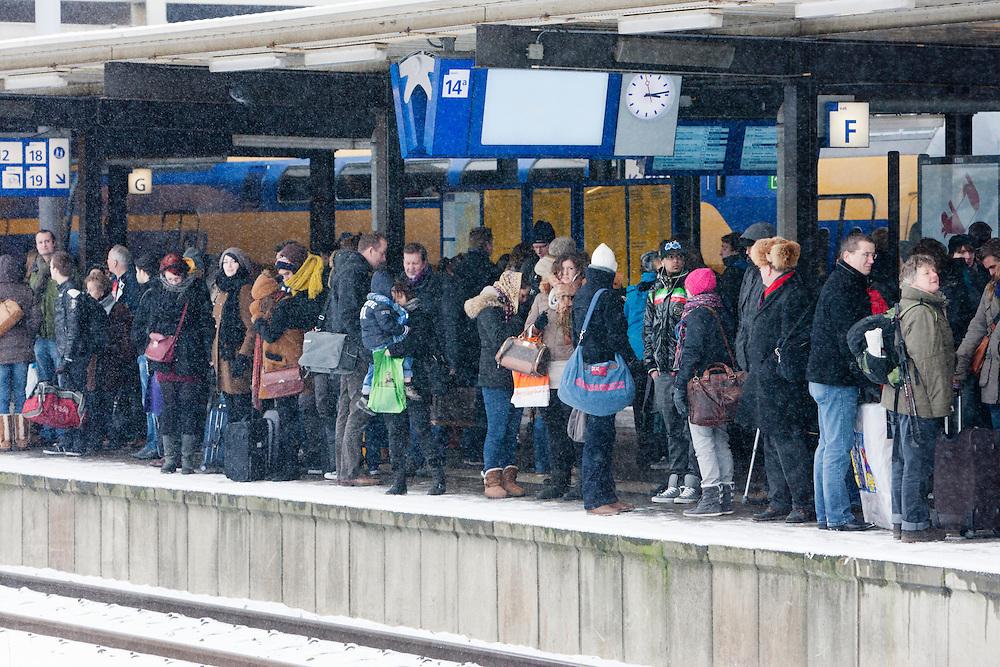 Reizigers wachten tevergeefs op een trein. Door sneeuwval is het treinverkeer ernstig ontregeld. Op Utrecht Centraal zijn veel reizigers gestrand. Slechts mondjesmaat rijdt een trein.<br /> <br /> Passengers are waiting in vain on a train at Utrecht CS. Due to the snow the Dutch railways are facing big problems. Lots of travelers are stuck on Utrecht Central Station. Only a few trains will depart.
