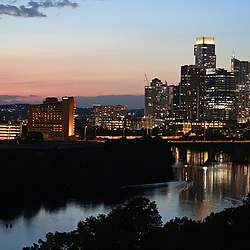 The City of Austin, TX  skyline is  reflecting in the waters of Lady Bird Lake looking west at sunset in mid-August. 2020.  Downtown Austin continues to boom despite the national economic slowdown.