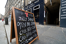 Edinburgh, Scotland, UK. 16 June, 2020. As shops open in England, Scottish shops and businesses remain closed, Streets are empty and pubs and shops are still closed with many boarded up. Bars might be allowed to open outside areas at end of week but currently they are only-permitted to serve drinks to takeaway. Pictured; Sign outside pub on Royal Mile offering takeaway and off-sales drinks. Iain Masterton/Alamy Live View.