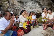 Nusa Penida, Indonesia - September 30, 2017: A Balinese family prays at a small temple at Peguyangan Waterfall on Nusa Penida, an island located off the coast of Bali.